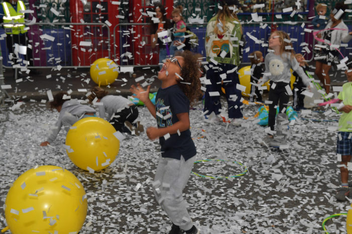 Photo of a child playing under falling confetti and balloons