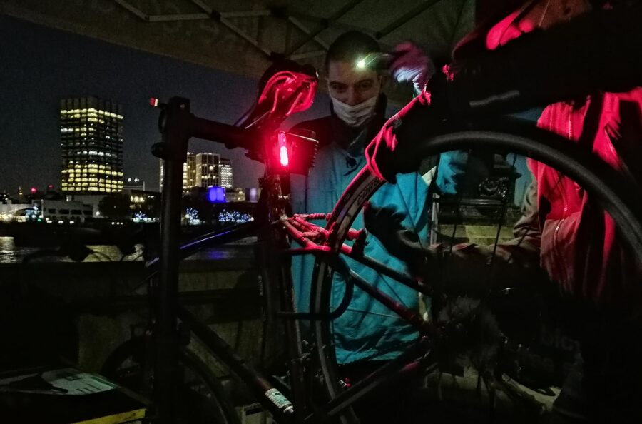 A photograph of a cycle mechanic fixing a cycle on Embankment at night.