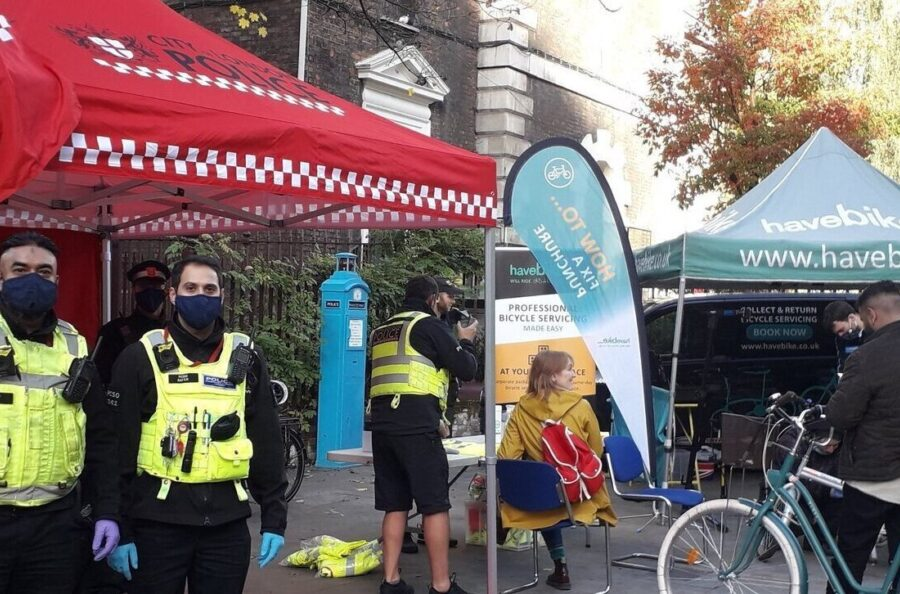 A photo of the Aldgate Community Cycling Event, with the police and Dr Bike all set up and ready to attend to peoples cycles.