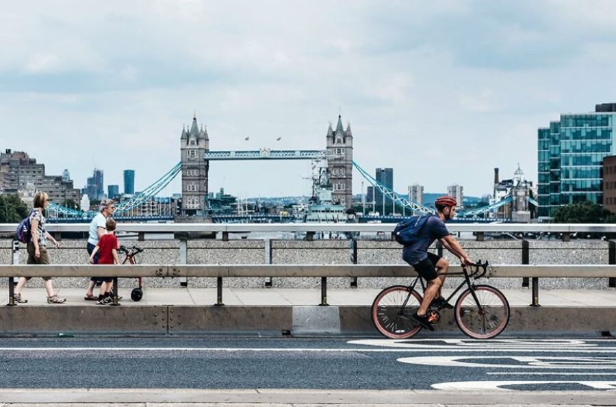 Cyclist and pedestrians walking across a bridge with Tower Bridge in the background