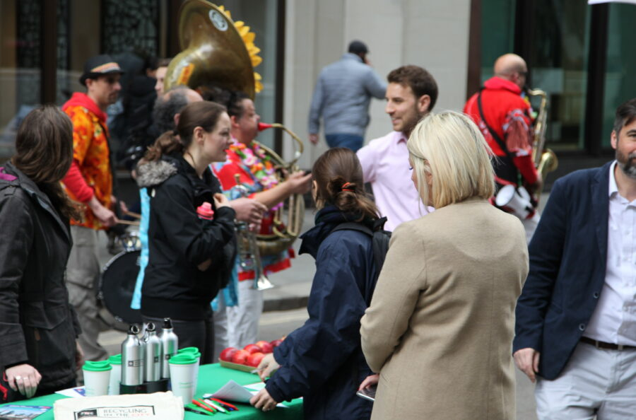 Photo of people enjoying music and people talking to stall holders at a Lunchtime Streets event