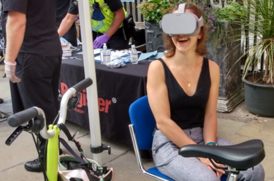 A woman wearing a Virtual Reality Headset enjoys the virtual reality exchanging places experience at St Batholomew's Hospital Road Safety Roadshow