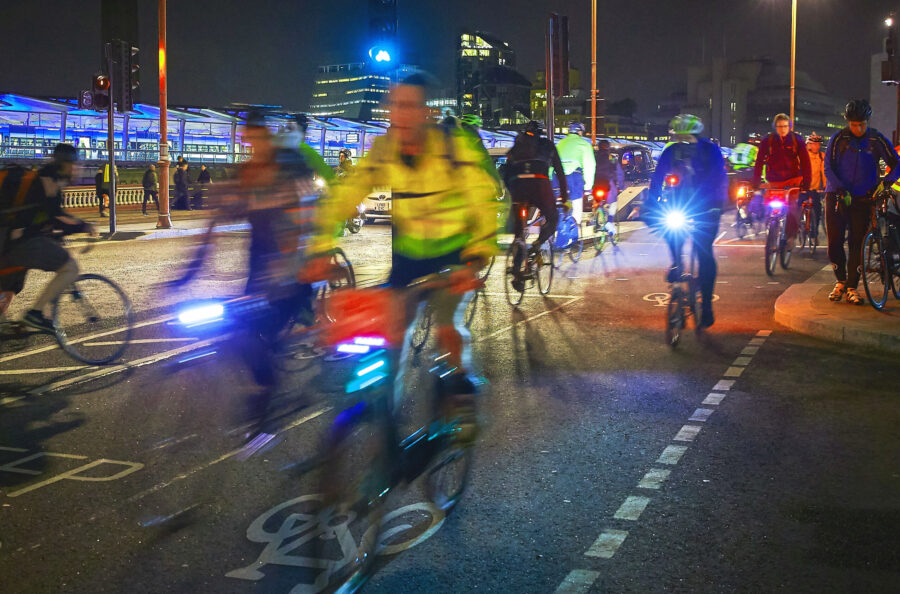 Image of people riding their cycles on Blackfriars Bridge at night