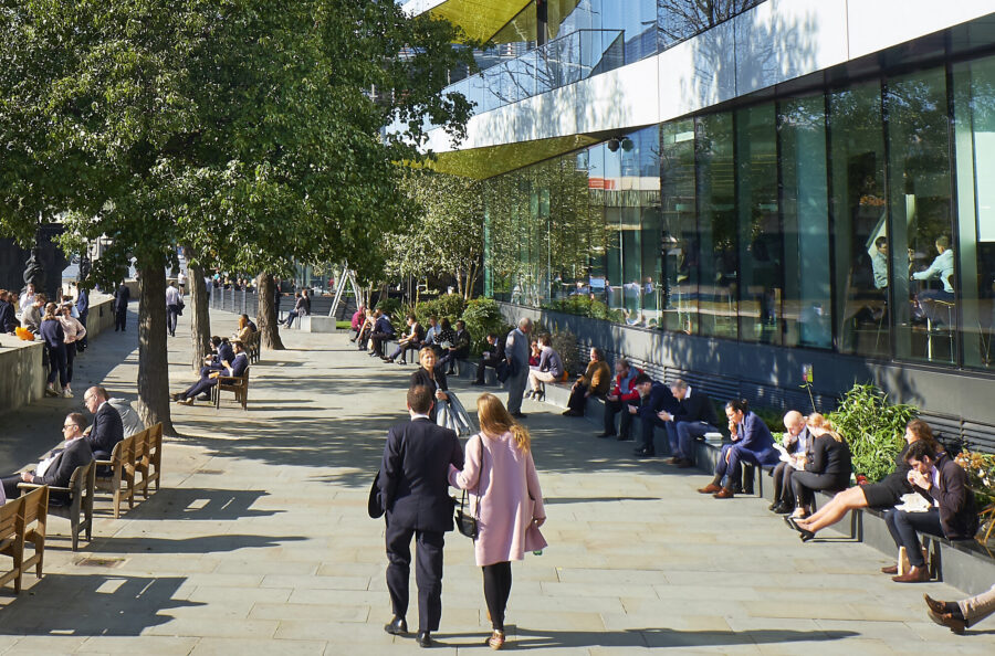 Image of people walking, sitting and enjoying a traffic free street along the river Thames in the City of London.