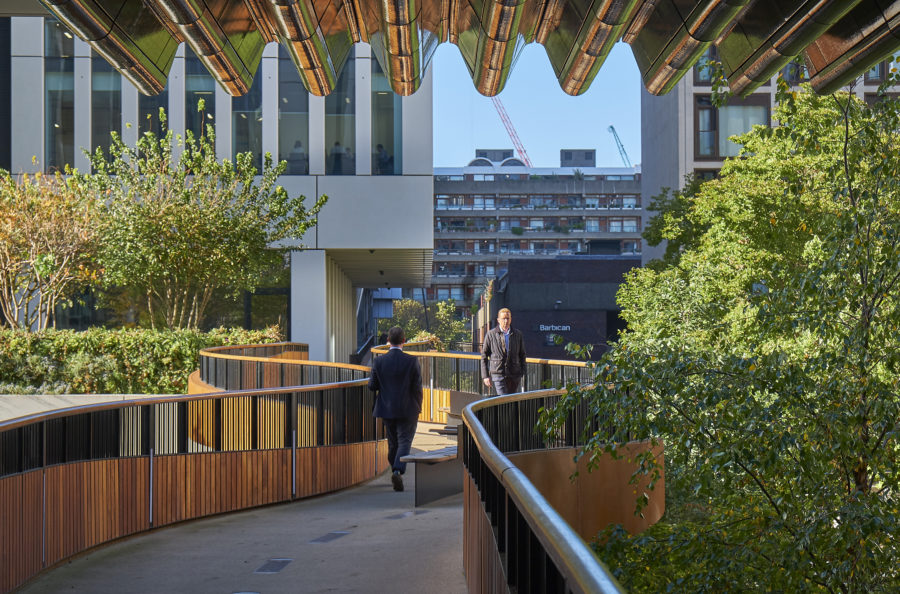 An image of two people walking along of of the highwalk bridges connecting to the Barbican.