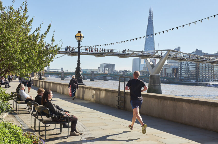 Photo of a person jogging and others enjoying the sun and view from benches along the pedestrian foot way of the Thames pass.