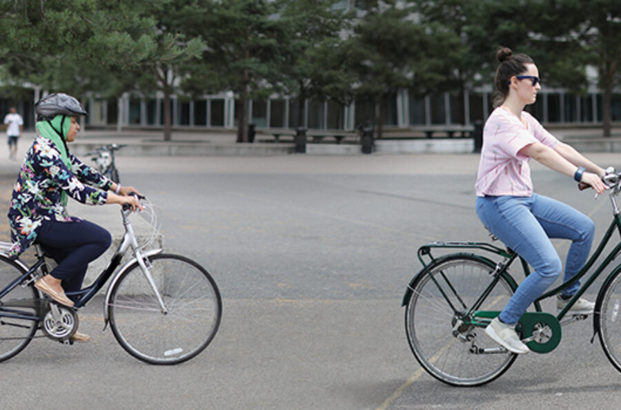 A photograph of two women cycling on a street in London